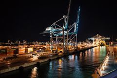 Maritime container port with cargo containers, cranes at night. Port or terminal with night illumination. Freight. Miami, USA - November, 23, 2015: maritime royalty free stock photo