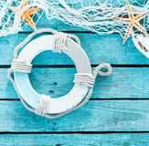 Maritime decoration with a life ring and fishnet. Maritime decoration in a themed background with copyspace on turquoise blue wooden planks decorated with a life Stock Images