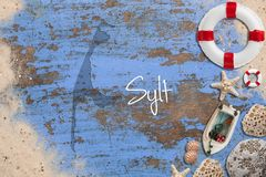 Maritime decoration and the shape of the island Sylt. Maritime decoration and the shape of the island `Sylt ` on blue wooden background royalty free stock images