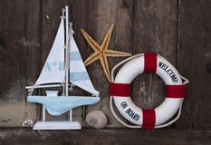Maritime Decoration with shells, starfish, sailing ship, fishing net on blue drift wood royalty free stock photo