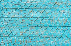 Maritime fishing net over turquoise blue wooden deck background. Fishing net texture on rustic blue wooden background with copy space royalty free stock photos