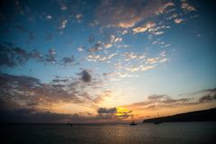 Maritime landscape at dawn with some boats in the background and an expressive sky with clouds. In a mediterranean island royalty free stock photos