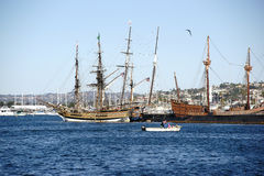 Maritime Museum San Diego. San Diego, United States - December 25, 2015: A motorboat passes the old and historic sailing ships of the maritime Museum San Diego stock photos
