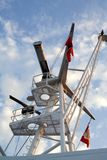 Maritime navigation mast. Low angle view of maritime communication and navigation mast on modern ship with blue sky and cloudscape background Stock Image