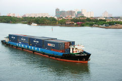 Maritime transport by loading container on river. HO CHI MINH CITY, VIET NAM- MARCH 12: Maritime transport on river, vessel loading container on water Stock Photo