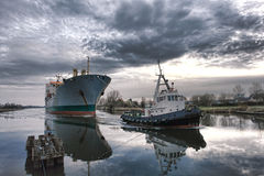 Maritime Tugboat Pulling a Cargo Ship on a Canal. Maritime tugboat pulling a large cargo ship on a navigation boat canal at dusk Royalty Free Stock Image