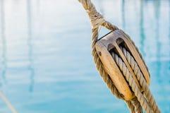 Maritimt nautiskt träblock med rep av den gamla seglingyachten med bakgrund för havsvatten arkivfoton