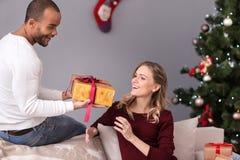 Marito amoroso allegro che dà un presente alla sua moglie immagine stock