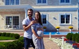 Marito amoroso e moglie incinta che posano davanti alla nuova h moderna immagini stock libere da diritti