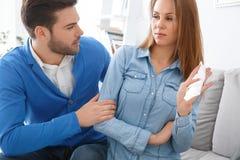 Marito aspettante di problemi della famiglia di sessione di psicologia delle giovani coppie che abbraccia gridando moglie immagini stock