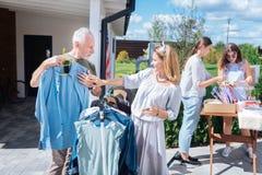 Marito barbuto che pensa a comprare nuova camicia blu alla vendita di oggetti usati fotografia stock