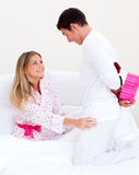 Marito bello che dà un presente alla sua moglie immagine stock