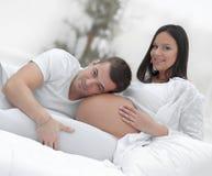 Marito che ascolta la sua pancia del ` s della moglie immagine stock libera da diritti