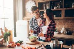 Marito che bacia moglie sulla cucina mentre lei che cucina fotografia stock