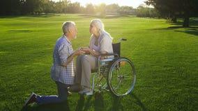 Marito che bacia tenero le mani della moglie sulla sedia a rotelle video d archivio