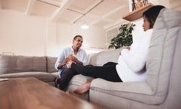 Marito che massaggia le sue gambe incinte della moglie immagini stock libere da diritti