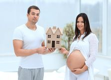 Marito che mostra alla sua moglie incinta una disposizione della loro casa futura fotografia stock libera da diritti