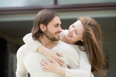 Marito d'abbraccio della giovane moglie dalla sua parte posteriore che gode dei outs di svago fotografia stock libera da diritti