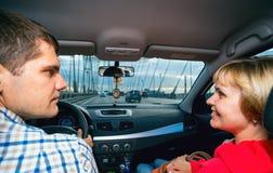 Marito e moglie che esaminano amoroso a vicenda nella velocità dell'automobile Fotografie Stock
