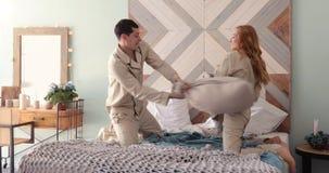 Marito e moglie che giocano con i cuscini sul letto archivi video