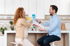 Marito e moglie che ridono fragorosamente nella cucina immagini stock libere da diritti