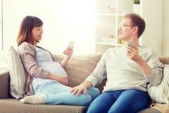 Marito e moglie incinta con lo smartphone a casa immagine stock