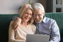 Marito e moglie maturi di risata felici divertendosi con il computer portatile fotografie stock libere da diritti