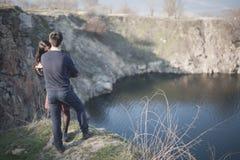 Marito e moglie sulla riva del lago con le rive rocciose, molla in anticipo Siluette degli amanti che entrano in acqua sulla part Immagini Stock