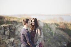 Marito e moglie sulla riva del lago con le rive rocciose, molla in anticipo Siluette degli amanti che entrano in acqua sulla part Fotografia Stock