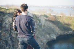 Marito e moglie sulla riva del lago con le rive rocciose, molla in anticipo Siluette degli amanti che entrano in acqua sulla part Fotografie Stock Libere da Diritti