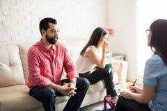 Marito e moglie tristi nel corso della riunione con il consulente di matrimonio immagine stock libera da diritti