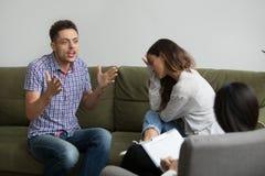 Marito emozionale che parla allo psicologo mentre moglie offensiva s Immagini Stock