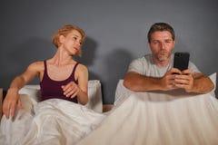 Marito o ragazzo che usando telefono cellulare a letto e ribaltamento frustrato sospettoso di sensibilità dell'amica o della mogl fotografia stock