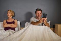 Marito o ragazzo che usando telefono cellulare a letto e ribaltamento frustrato sospettoso di sensibilità dell'amica o della mogl immagine stock