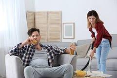 Marito pigro che guarda TV e la sua pulizia della moglie fotografie stock libere da diritti