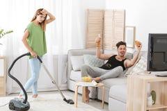 Marito pigro che guarda TV e la sua pulizia della moglie fotografia stock libera da diritti