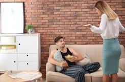 Marito pigro che litiga con la moglie laboriosa fotografia stock