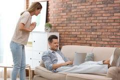 Marito pigro che litiga con la moglie laboriosa fotografie stock