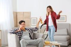 Marito pigro che litiga con la moglie laboriosa immagini stock