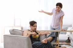 Marito pigro che litiga con la moglie laboriosa fotografia stock libera da diritti