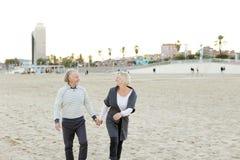 Marito senior e moglie sorridente che corrono sulla spiaggia di sabbia e sul tenersi per mano immagini stock libere da diritti