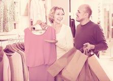 Marito senior positivo che aiuta moglie affascinante a selezionare vestito Fotografia Stock Libera da Diritti