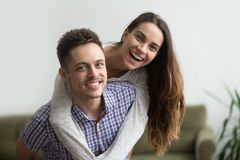 Marito sorridente che trasporta sulle spalle moglie allegra a casa, coppie felici Immagini Stock Libere da Diritti