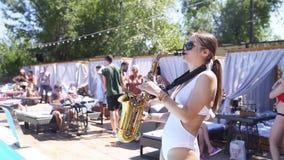 Mariupol, Ucraina - 15 giugno 2019 Signora attraente del sassofonista sta giocando il sassofono vicino allo stagno al club della  video d archivio