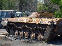 MARIUPOL, UKRAINE-MAY 09,2014: Zniszczony opancerzony samochód na stree Obrazy Stock