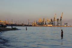 MARIUPOL, UKRAINE - 5. SEPTEMBER 2016: Schattenbild vieler großes Kräne im Hafen am goldenen Licht des Sonnenuntergangs Stockfotos
