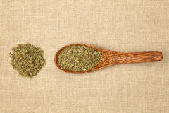 Marjoram spice. Dry marjoram spice on bamboo spoon on brown bacground, top view Stock Photos