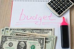 Markörpennor, räknemaskinen, sedlar och anteckningsboken med inskriften budgeterar på trätabellen arkivbild