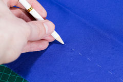 Mark cloth with special white pen. Before making the cut Royalty Free Stock Photo