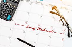 Mark long weekend on calendar. Mark long weekend on calendar with eyeglasses and calculator Royalty Free Stock Photos